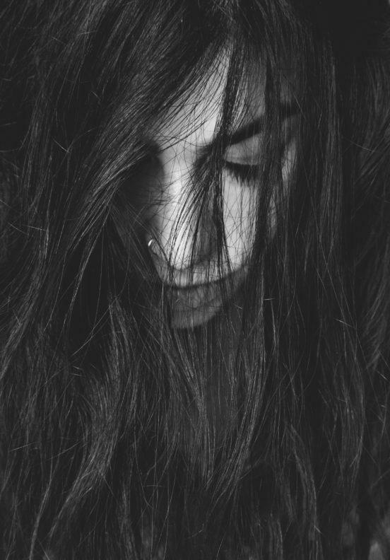 Eine junge Frau mit Piercing und braunen Haaren - man sieht nur ihr Gesicht... und viele Haare. Sie gefällt mir.