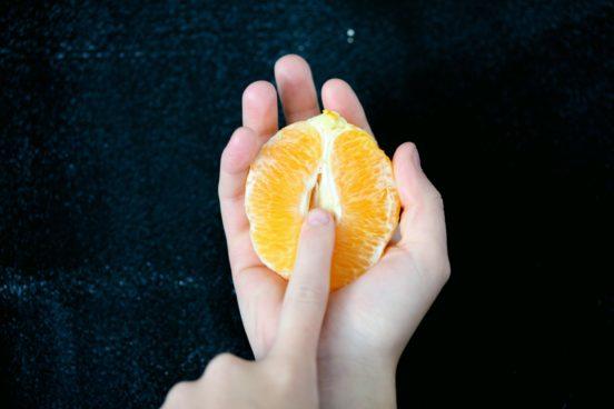 Ein Finger und das Innenleben einer Orange