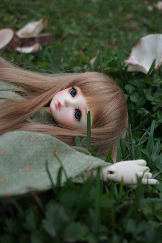 eine Puppe liegt im Gras und schaut gen Himmel.