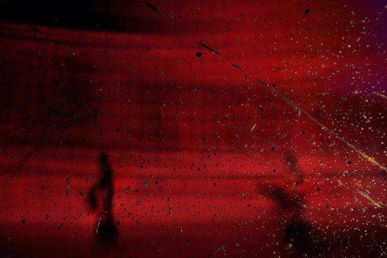 Rot - vermutlich Wassertropfen auf einer Scheibe und rotes Licht.