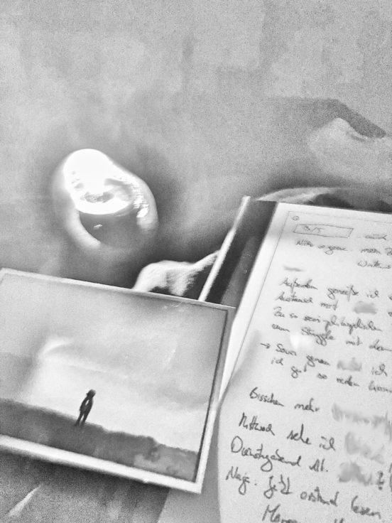 Eine Kerze, eine Postkarte, ein Journal - im Bett, grau eingefärbt.