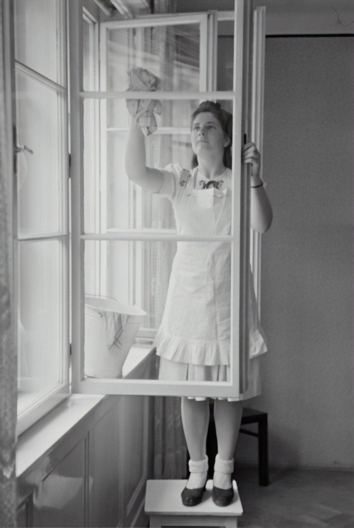 Fräulein putzt auf einem Hocker stehende Fenster.