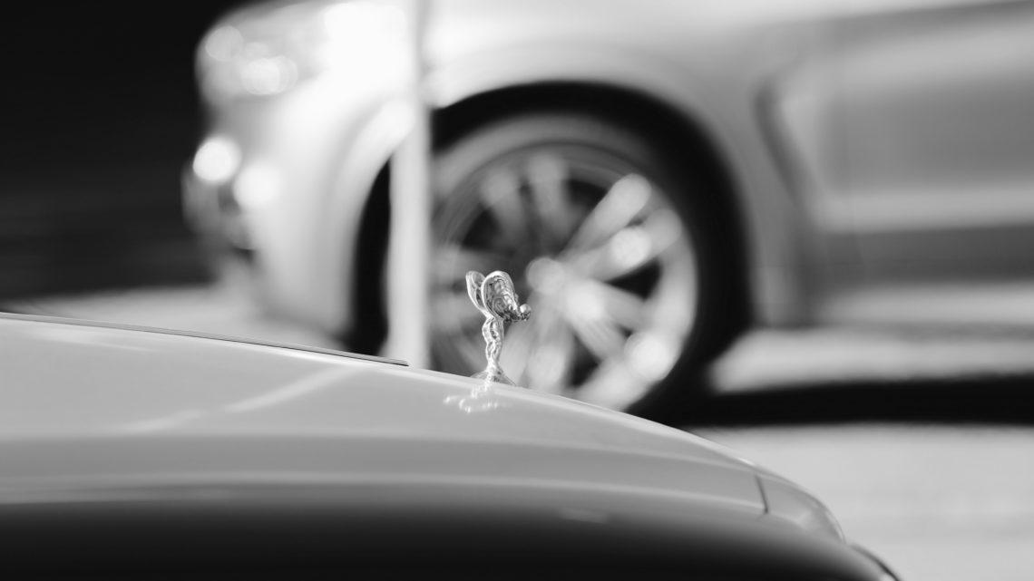 Rolls-Royce Kühlerfigur. Im Hintergrund glänzende Felgen.