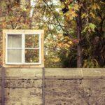 Ein Fenster auf einer Mauer, vor einem herbstlichen Baum - es ist halb durchsichtig.